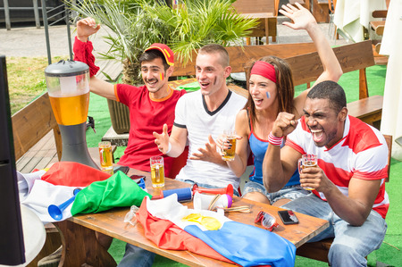 Young football supporter fans cheering with beer watching soccer match - Friends people with multicolored soccer tshirts and flags having fun - Sport championship concept - Warm afternoon color tones Stockfoto