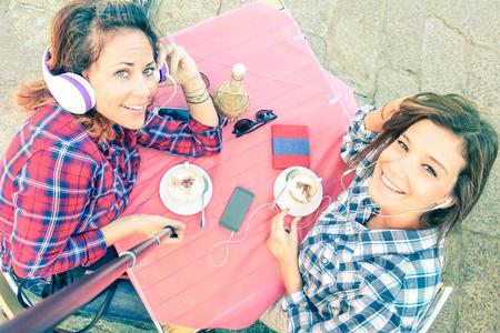 capuchino: Vista superior de amigas inconformista que toman autofoto con el palillo - concepto Mujer amistad con muchachas que beben cappuccino en el restaurante cafetería - Mejores amigos que se divierten juntos - cuarzo tono de color rosa