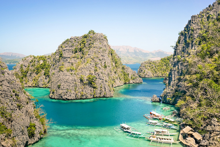 Blue lagoon with longtail boats by Karangan Lake in Coron Palawan - Beautiful tropical destination in Philippines - Travel concept to nature wonders around the world - Warm sunny afternoon color tones