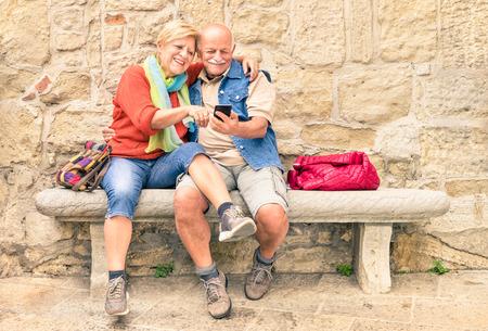 Happy senior paar plezier samen met mobiele smart phone - Begrip actieve speelse ouderen tijdens het pensioen - Reizen lifestyle concept met gepensioneerden - Warm bewolkte middag kleurtinten Stockfoto