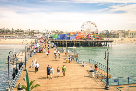 pier: LOS ANGELES - 18 MARCH 2015: high angle view of international tourists and local people at Santa Monica Pier with ferris wheel of Pacific Amusement Park - Famous american landmark on californian coast