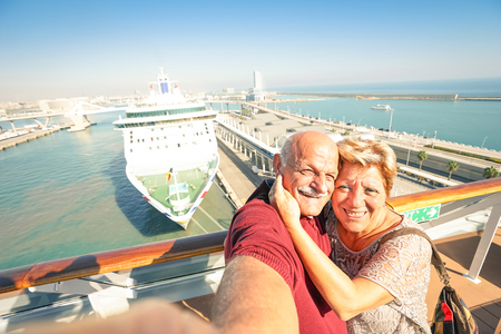 Senior happy couple taking selfie on ship at Barcelona harbour background - Mediterranean cruise travel tour - Active elderly concept with retired people around the world - Warm afternoon color tones