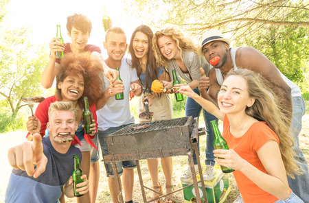 Happy multiracial friends having fun at picnic barbecue garden party - Friendship concept with multiethnic people taking group photo with barbeque grilled food - Warm filter with enhanced sushine halo