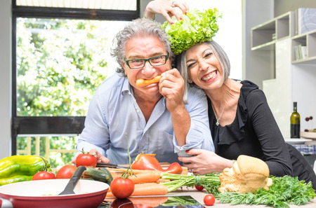 healthy lunch: Senior couple having fun in kitchen with healthy food - Retired people cooking meal at home with man and woman preparing lunch with bio vegetables - Happy elderly concept with mature funny pensioner
