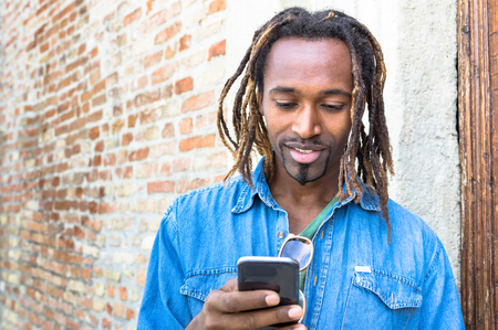 guy person: African american young man using mobile smart phone - Hipster guy model with modern smartphone - Male trendy person with cellphone and dreadlocks hairstyle - Concept of integration and new technology Stock Photo