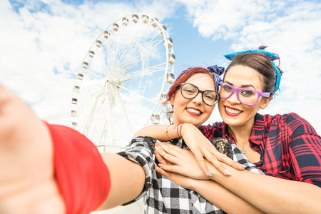 best: Young women girlfriends taking selfie at ferris wheel on public Rimini beach - Friendship concept with pin up girls having fun together - Best female friends catching the moment with modern smartphone Stock Photo