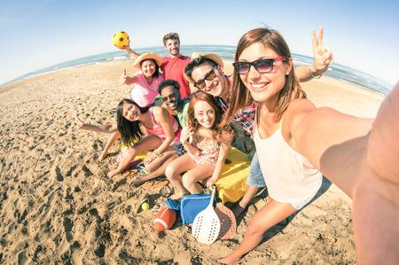 Groep multiraciale gelukkige vrienden nemen selfie en plezier met beach sport spellen - Summer concept van vreugde en multi-etnische vriendschap - Zonnige middag kleurtonen met focus op meisje bedrijf camera Stockfoto