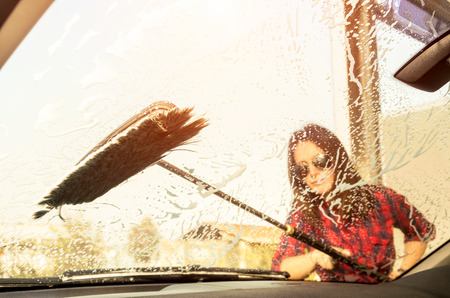 dirty car: Inside view through the glass of pretty woman at carwash - Emancipation concept with young woman washing car - Focus on the brush - Warm vintage filtered look with enhanced sunflare halo