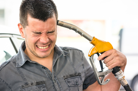 Young man in suicide mimic position at fuel gas station - Gasoline price rising concept with desperate guy pointing pump nozzles pistol on head - Shallow depth of field with focus on closed eyes Stok Fotoğraf - 58784136