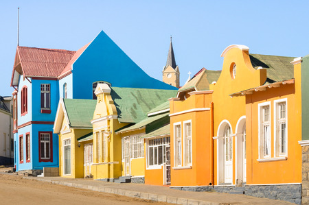 luderitz: Colorful houses in Luderitz - Architecture concept with ancient german style town in south Namibia - Exclusive travel destination in african european settlement - Warm afternoon color tones Stock Photo