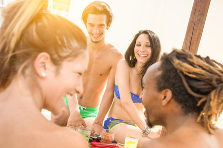 multi racial: Multiracial friends having genuine fun at beach - Summer concept with young multi racial people talking and drinking cocktail - Tilted composition with focus on couple in background - Warm filter look Stock Photo