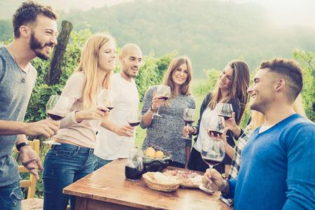 Gelukkige vrienden plezier outdoor - Jonge mensen genieten van de oogst tijd samen bij boerderij wijngaard platteland - Jeugd en vriendschap concept - ondiepe diepte van het veld met desaturated vintage filter Stockfoto