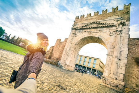 Man following beloved woman on autumn vacation - Fun concept with travelers in Rimini old town at Augustus Arch - Boyfriend and girlfriend around the world - Vivid contrast filter with enhanced sunset