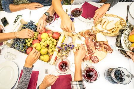 top angle view: Top view of friend hands eating food and wine at barbecue garden party - People group enjoying fruit and sliced sausages at backyard meeting - Lunch and dinner concept outdoors - Bright vivid filter