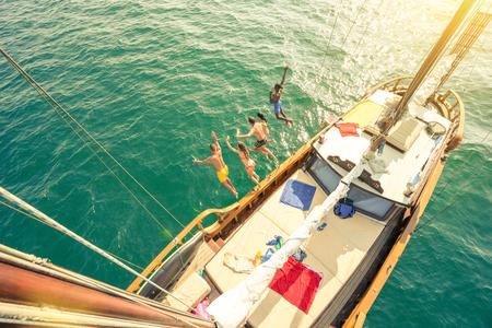 Vue aérienne de jeunes sautant d'un bateau à voile lors d'un voyage en mer - Rich amis heureux s'amusant pendant la fête d'été - Concept de vacances exclusif - Filtre vintage chaleureux avec halos de lumière parasite améliorés Banque d'images