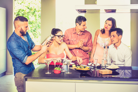 Groep vrienden die pret hebben bij house party met pre diner aperitief cocktails en het eten van snacks - Jonge mensen besteden tijd samen thuis