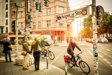 going places: BERLIN, GERMANY - OCTOBER 7, 2016: motion view of everyday life with bikers and pedestrians at beginning of Box Hagener Strasse in the area of Friedrichshain at sunset - Warm vintage vignetted filter