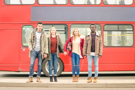 vida social: Group of fashion friends crossing the road with typical red bus behind - Autumn winter concept of social life with young people hanging out together - Neutral color tones with focus in guys and girls Foto de archivo