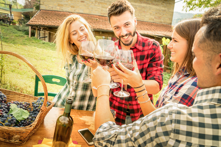 people: Happy friends having fun and drinking wine - Friendship concept with young people enjoying harvest time together at farmhouse vineyard countryside - Warm filter with focus on faces in center of frame
