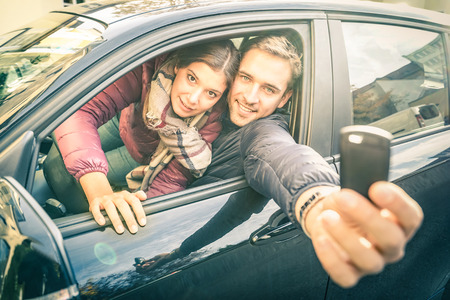 open autocar auto: Happy couple at car rent showing electronic key ready for the next road trip - Transportation and vehicle loan concept with satisfied people at rental service - Soft backlighting and desat filter