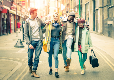 Happy multiracial friends walking on Brick Lane at Shoreditch in London - Friendship concept with multicultural young people on hipster cloths having fun together - Soft focus and desat vintage filter 스톡 콘텐츠
