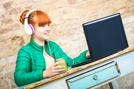 face work: Hipster redhead woman with headphone using laptop drinking cocktail and having fun at work - Modern concept of professional engagement connected with happy and productive attitude - Focus on girl face
