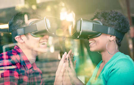enhanced: Multiracial couple in love going beyond racial diversity through virtual reality glasses - Young people having fun using new technology - Composition with window reflection on enhanced sun flare halo Stock Photo