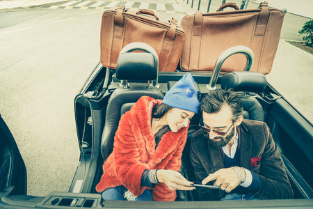 cabrio: Happy couple having fun with satnav at car travel - Hipster guy having fun with fashion girlfriend at road trip - Love relationship concept with young people on tour together - Soft retro lomo filter Stock Photo