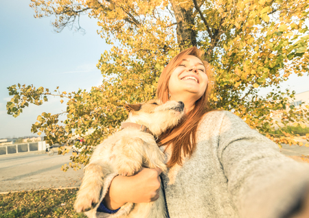 Young redhead woman taking surprised selfie outdoors with cute dog on spontaneous face expression - Friendship concept between people and animals - Warm sunny afternoon color tones in autumn day