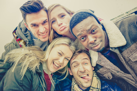 Best friends taking selfie outdoor on autumn winter clothes - Happy youth concept with multiracial people having fun together photo