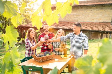 Heureux amis ayant de boire du vin plaisir à cave viticole - concept d'amitié avec jeunes profitant moment de la récolte ensemble à ferme - Filtre chaud avec améliorer soleil flare auréole - Feuilles en cadre Banque d'images