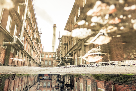 urban decay: Puddle reflection of abandoned factory in Saint Petersburg neighborhood in Russia - Urban decay concept with forgotten places around the world - Soft focus due to water reflection - Retro desat filter