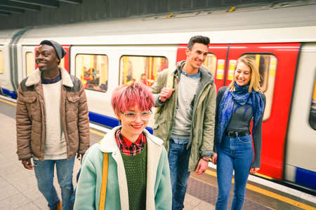 strangers: Multiracial group of hipster friends having fun in tube subway station - Urban friendship concept with young people walking together in city underground area - Vivid color with focus on pink hair girl