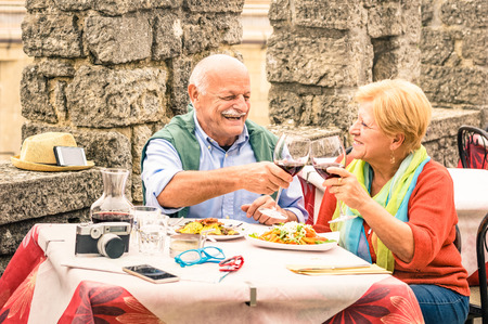 Senior couple having fun and eating at restaurant during travel - Mature man and woman wife in old city town bar during active elderly vacation - Happy retirement concept with retired people together Stock Photo - 65594943
