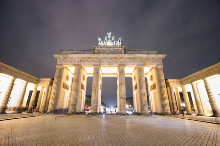 Front view of Brandenburg Gate in Berlin by night - Travel concept with beautiful places landmark in world famous european capital - Composition with wide angle distortion and nightscene color tones