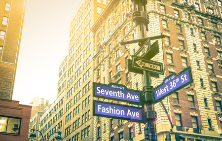 Street sign of Seventh and Fashion Ave with West 36th St at sunset in New York City - Urban concept and road direction in Manhattan - American world famous capital destination on warm vintage filter Фото со стока