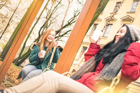 having fun in winter time: Happy girlfriends having fun on swing game at park in autumn season - Friendship concept with joyful girls sharing winter time together - Warm filter and sun flare halo with focus on blond young woman Stock Photo