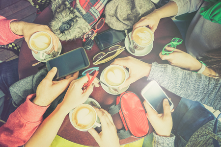 mobile phones: Group of friends drinking cappuccino at coffee bar restaurant - People hands using smartphone on upper point of view - Technology concept with addicted men and women - Lomo vintage filter with halo