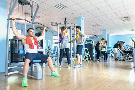 weight room: Small group of sportive friends at gym fitness club center - Happy sporty people interacting in weight room training - Social gathering concept in sport lifestyle context - Main focus in middle frame