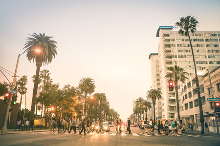 Locals and tourists walking on zebra crossing and on Ocean Ave in Santa Monica after sunset - Crowded streets of Los Angeles and California state - Warm desat twilight color tones with blurred people