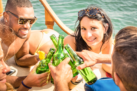 Multiracial people on yacht drinking together - Group of rich friends toasting beer and having party on sailing boat - Luxury travel concept with happy talking and laughing situation - Focus on woman