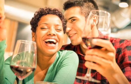 arouse: Happy multiracial couple of lover drinking red wine at fashion restaurant - Handsome man whispers soft kisses in beautiful woman ear - Relationship concept with boyfriend and girlfriend on warm filter