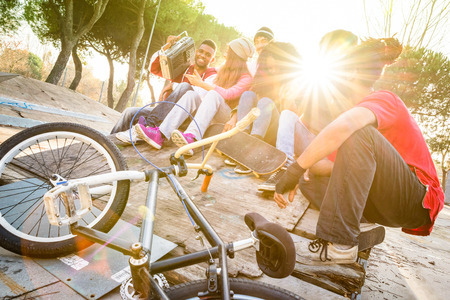 party friends: Group of trendy friends having fun together at skate bmx park  - Youth friendship  concept with young people outdoors - Focus on afroamerican guy with stereo - Retro vibrant filter with sunflare halo