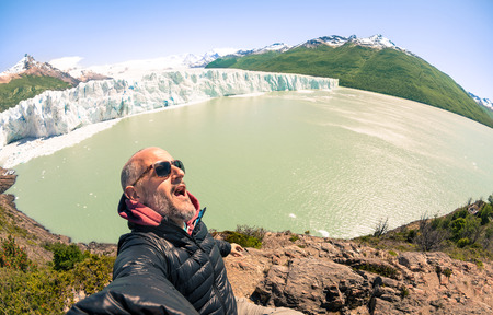 calving: Young man solo traveler taking selfie at Perito Moreno glaciar in south american argentinian Patagonia - Adventure wanderlust concept on world famous nature wonder in Argentina - Warm turquoise filter