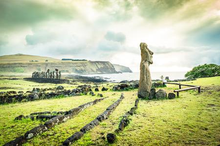 ki: Moai Haere Ki Haho  The Traveling Statue  at the entrance of Ahu Tongariki spot area on world famous Easter Island in Chile - Travel wanderlust concept - Vivid green filter on dramatic cloudy sky Stock Photo