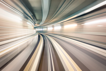 Subway underground tunnel with blurry rail tracks in metro gallery - Modern concept of public transport and connection - Radial zoomed speedness of railway space - Soft focus due to motion blur Stock Photo