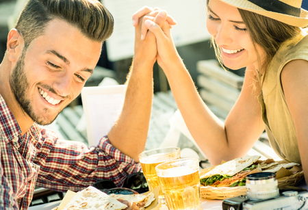 Couple in love taking selfie at beer bar on travel excursion - Young happy tourists enjoyng happiness moment at street food restaurant - Relationship concept with soft focus and desat contrast filter