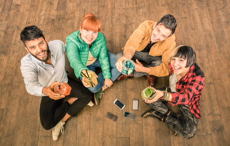 young entrepreneurs: Group of hipster best friends with smartphones in grungy alternative location - Young entrepreneurs people resting at cocktail bar renovation - Friendship fun concept with trend technology interaction Stock Photo