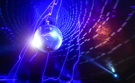 Disco ball laser show in modern disco party night club with bright spotlight - Concept of nightlife with music and entertainment - Image with powered colored halos and vivid glowing lights Imagens