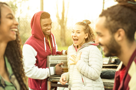 couples outdoors: Group of multiracial friend couples having fun time out at park in autumn winter time - Youth friendship concept with people together outdoors - Focus on blond young woman - Warm contrasted filter